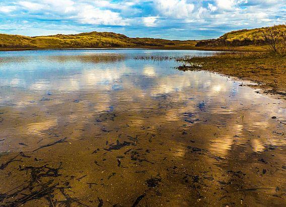 Een heldere winterdag in de duinen met witte wolken in 't water