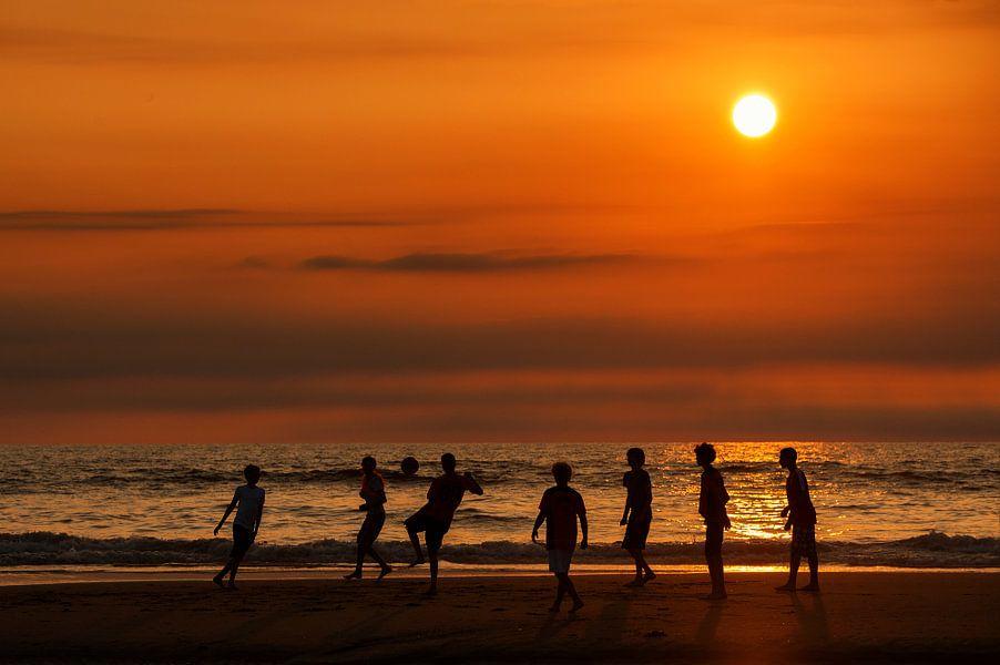 Strandvoetbal bij zonsondergang