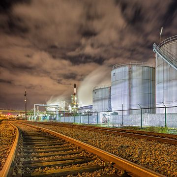 Olieraffinaderij in de nacht met rails en silo's tegen een bewolkte hemel van Tony Vingerhoets