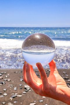 Hand mit Glaskugel auf Strand Ufer und Meer von