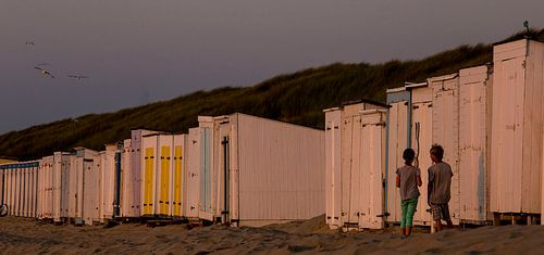 Kinderen staan eenzaam voor een gesloten strandcabine met een afbeelding van Nijntje aan het strand,