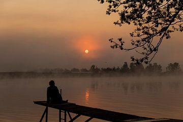 een silhouet van een vrouw die zit aan de maas tijdens zonsopkomst van Compuinfoto .