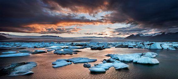 A glowing sunset over the glacier lagoon in Iceland van Olga Ilina