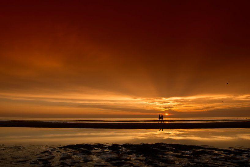 Wandelaars tijdens zonsondergang van Dick van Duijn