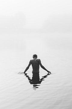 Ein Junge steht in einem nebelumhüllten See. von Robin van Steen