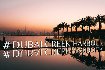 # Dubai Creek Harbour mit Palmen, der Skyline und dem orangefarbenen Himmel nach Sonnenuntergang