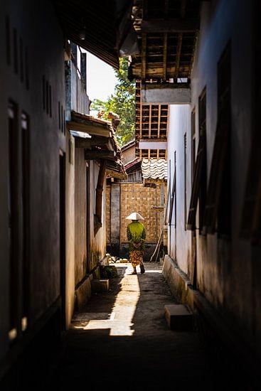 Oude dame wandelt door het dorp in traditionele Indonesische batik kleding.