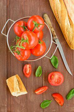 Frische Tomaten liegen in einem Küchensieb auf einem Holztablett von Edith Albuschat