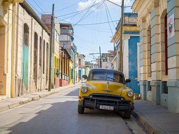 Gele oldtimer in de staten van Santiago de Cuba van Teun Janssen