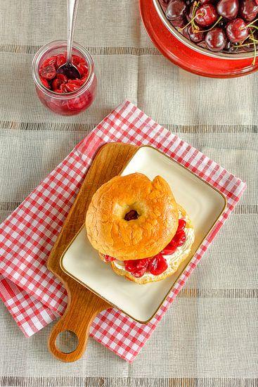 Ein selbst gebackener Bagel mit Frischkäse und Kirschmarmelade liegt auf einem Teller
