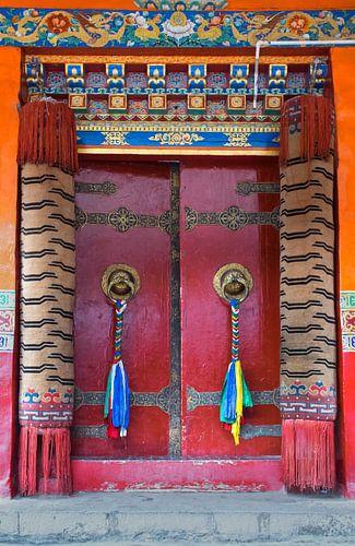 Rode deur met gebedsvlaggen in een Tibetaans klooster