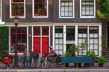 Grachtenpand in Amsterdam met rode deuren en motorrijder in rood van Suzan Baars