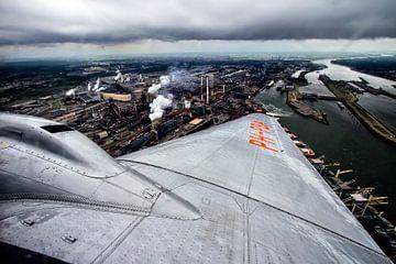 klassiek DC-3 vliegtuig vliegend over Tata Steel IJmuiden (Hoogovens) van Jeffrey Schaefer