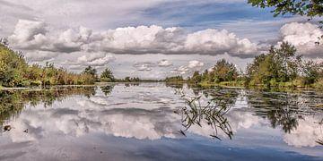 Wolkenlucht weerspiegeld in het water van De Deelen in Friesland van Harrie Muis
