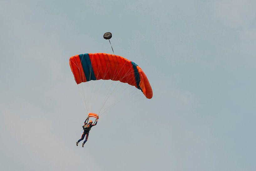 Parachutist tegen een blauwe lucht aan een blauw-oranje parachute van Tonko Oosterink