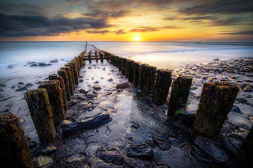 Golfbreker bij zonsondergang aan de Zeeuwse kust