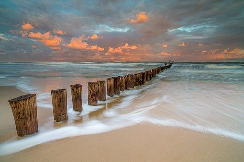 Paaltjes in zee tijdens zonsondergang