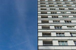 tweeluik wit flatgebouw en blauwe lucht
