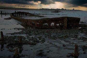 Zonsondergang aan de Waddenzee met een scheepswrak van
