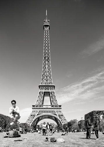 Springende man bij Eiffeltoren in Parijs in zwart-wit