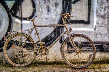 Oude vuile fiets op muur met graffiti van Dieter Walther