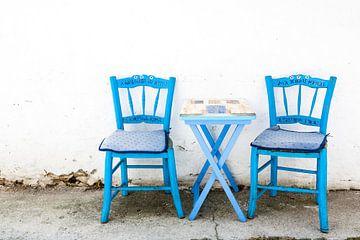 Blauwe tafel en stoelen in een Grieks steegje. van Victor van Dijk