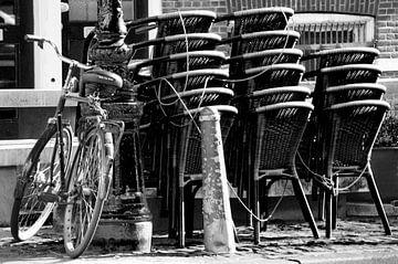 Fahrrad gegen Stange mit gestapelten Stühlen von Marion Hesseling
