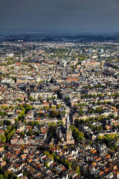 Luchtopname van de binnenstad van Amsterdam met de Westerkerk in de voorgrond en een zwarte regenbui van Marco van Middelkoop