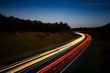 Verkeer op een snelweg door de natuur in de nacht van Sjoerd van der Wal