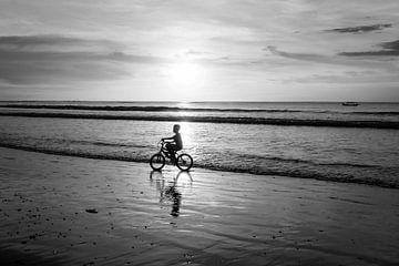 Zwart wit fotografie van fietser aan de kustlijn op het prachtige eiland Bali. van Mariëlle Debrichy