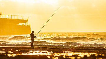 Hengelaar op het strand in de zonsondergang van videomundum