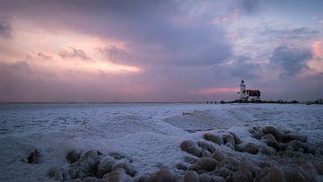 Leuchtturm in Marken bei Sonnenaufgang im Winter mit vielen Eis. von Ralph Rozema