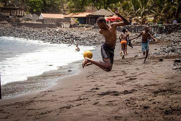 Afrikaanse jongen voetbalt op het strand van Julian Buijzen