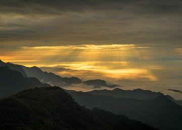 Zonneharpen en wolken in de bergen van Alishan in Taiwan. van Jos Pannekoek