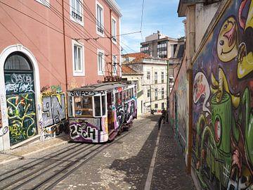 Oude tram en graffiti in een steeg in Lissabon van Sofie Duchateau