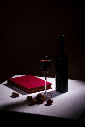 Stilleven met rode wijn en een boek
