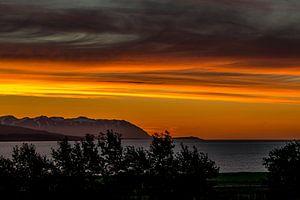 Oranje avondlucht in IJsland uitkijkend over een fjord richting de oceaan