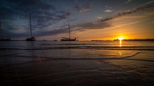Bootjes aan de horizon in de ondergaande zon