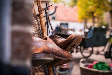 Versleten ouden leren schoenen opgehangen aan schoenveter van Fotografiecor .nl
