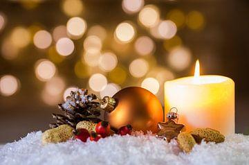 Brandende kaars en Kerstmisdecoratie over sneeuw en vage lichtenachtergrond met feestelijke stemming van Alex Winter