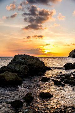 Rotsen in zee bij kleurrijke zonsondergang van Joke Van Eeghem
