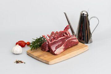 Lamsrack met paar ingrediënten zoals knoflook, rozemarijn , peperkorrels, tomaatjes en olijfolie van Wim Stolwerk