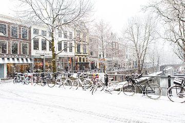 Winter in Utrecht. Besneeuwde fietsen op de brug over de Oudegracht. van De Utrechtse Grachten