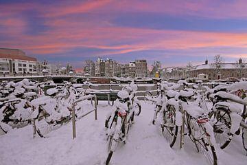 Besneeuwd Amsterdam in de winter bij zonsondergang van