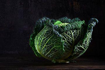 groene savooiekool, een gezonde wintergroente in dramatisch licht op donker en humeurig rustiek hout van Maren Winter