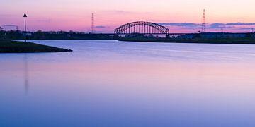 Brug over rivier tegen roze lucht von Fokko Erhart
