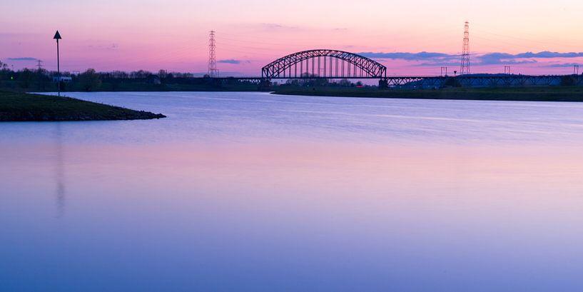 Brug over rivier tegen roze lucht van Fokko Erhart
