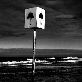 Afbeelding van een bord met paraplu op het strand bij Petten van Wim Stolwerk