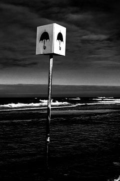 Bild eines Schildes mit Sonnenschirm am Strand bei Petten von Wim Stolwerk