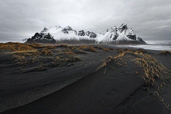 Bergkette vor schwarzen Sanddünen